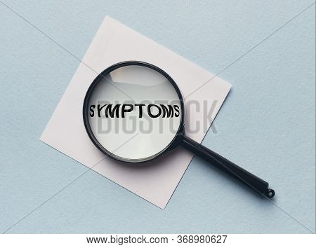 The Word Symptoms On White Paper Through Loupe Magnifying Glass. Medical Symptoms Concept