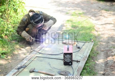 Old Man Welder In Brown Uniform, Welding Mask And Welders Leathers, Weld Metal Door With Arc Welding