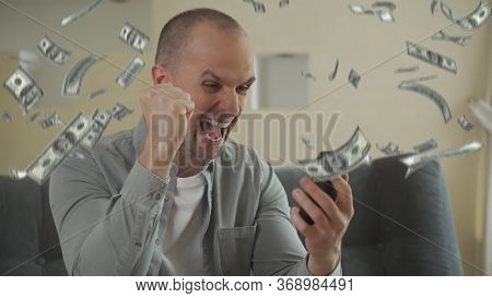 Man Using Smartphone And Winning Big Money On Sports Betting. Guy Sitting On Sofa And Rejoicing Vict