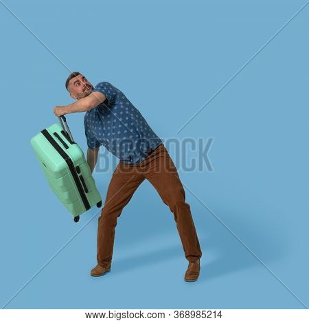 Man Holds Plastic Suitcase Posing In Studio On Blue Background. Caucasian Man Going To Throw His Gre
