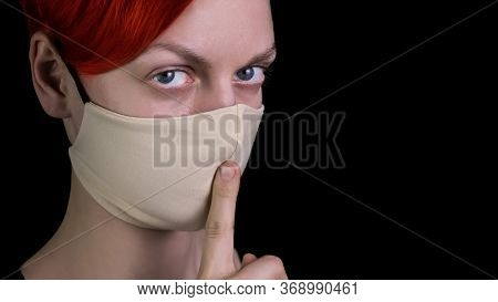 Portrait Of Red-haired, Young Woman In Protective Mask Showing Gesture Silence On Black Background,