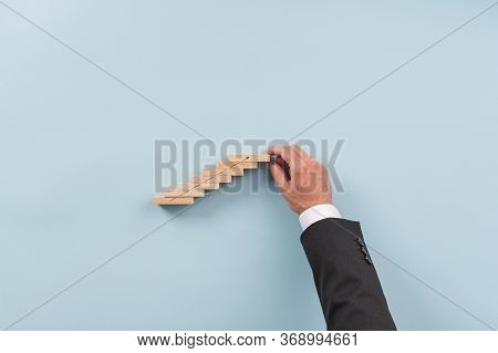 Hand Of A Businessman Building Stairwayof Wooden Pegs With An Upward Pointing Arrow. Conceptual Imag