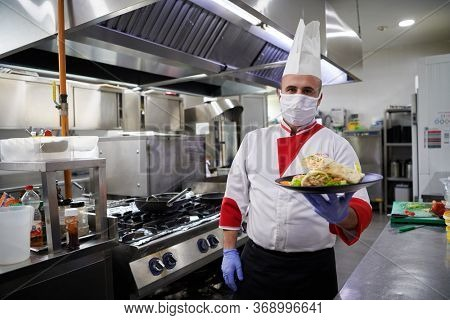 chef cook wearing face protective mask for corona virus disease with plate of authentic sandwich at professional restaurant kitchen. Health, safety distancing and pandemic in new normal concept