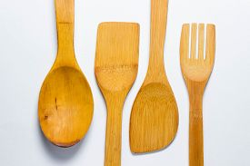 Four Wooden Cutlery Lie On Two Different Sides On A White Background. Wooden Spoon, Wooden Fork. And