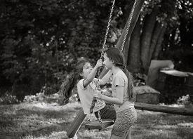 Two Happy Beautiful Girls Playing On Swing And Smiling At Warm  Summer Day