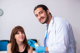 Young woman visiting male doctor dermatologist