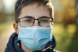 Guy In Glasses And In Medical Mask On The Street Health Care Concept.
