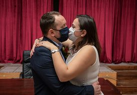 Groom And Bride Kissing Each Other In Protective Medical Masks On Face In