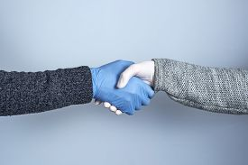 Shaking Hands In Medical Gloves On A Gray Background. The Concept Of A Safe Handshake.