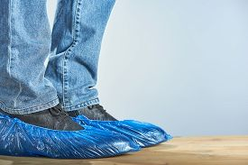 Man With Blue Shoe Covers Worn Over Classic Shoes On Gray Background, Closeup. Photo With Copy Space