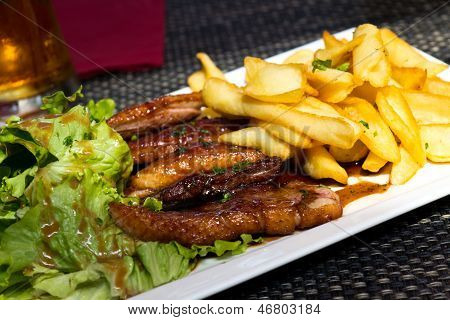 Roasted duck with french fries, potatoes, caramelized, and Salad