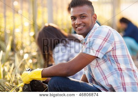 handsome teen volunteer cleaning streets with friends