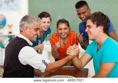 friendly middle aged teacher arm wrestling with high school student in classroom during break