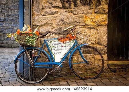 Old blue bicycle leaning agains stone wall