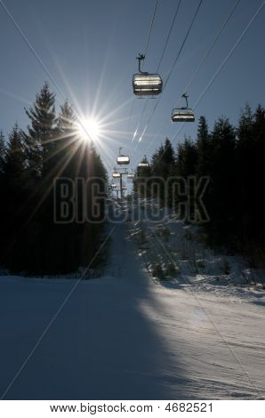 Chair Lift At Ski Resort, Backlit Trees