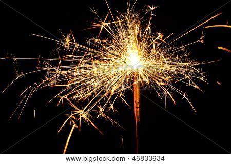 burning christmas sparkler isolated on blue background