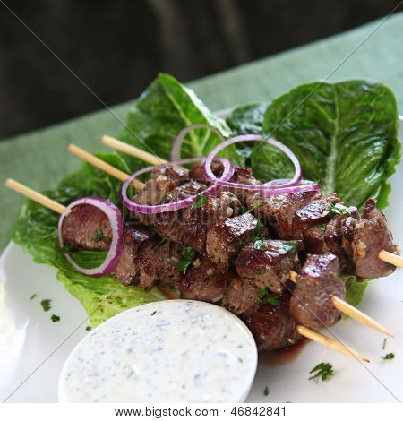 Lamb kebabs with tzatziki yogurt and red onions.