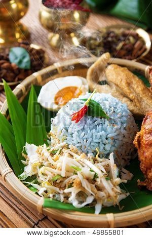 Nasi kerabu is a type of nasi ulam, popular delicious Malay rice dish. Blue color of rice resulting from the petals of  butterfly-pea flowers. Traditional Malaysian food, Asian cuisine.