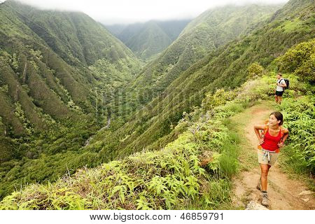 Hiking people on Hawaii, Waihee ridge trail, Maui, USA. Young woman and man hikers walking in beautiful lush Hawaiian forest nature landscape in mountains. Asian woman hiker in foreground.