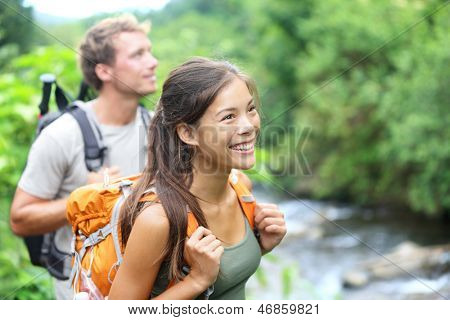 People hiking - happy hiker couple trekking as part of healthy lifestyle outdoors activity. Young multiracial couple walking in nature in Iao Valley State Park, Wailuku, Maui, Hawaii, USA.