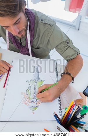 Fashion designer drawing a coat with pencils