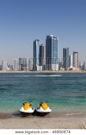 Two jet ski at the Sharja beach with sharja skyline in the background. image no 214. poster