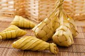 Ketupat or packed rice dumpling. Delicious traditional Malay ramadan food. Popular Malaysian food on bamboo mat. poster