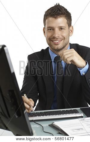 Happy young businessman working with computer, sitting at desk, looking at camera.
