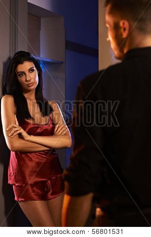 Sexy woman in red silk pyjamas looking sulky to man.