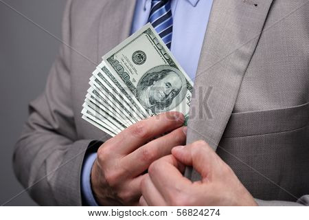 Man putting money in suit jacket pocket concept for corruption, bribing, paying or business wealth