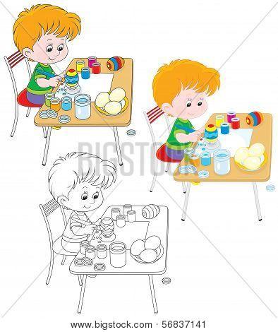 Boy paints Easter eggs