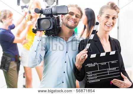Team or Cameraman with camera and woman with take clap or board on Film Set