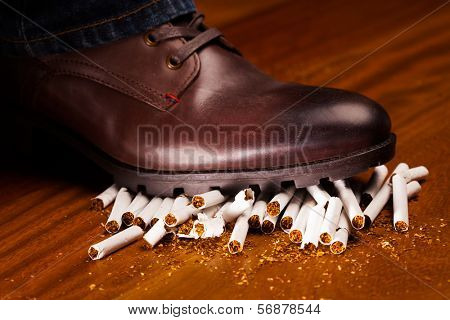 shoes trampling down on cigarettes - give up smoking concept