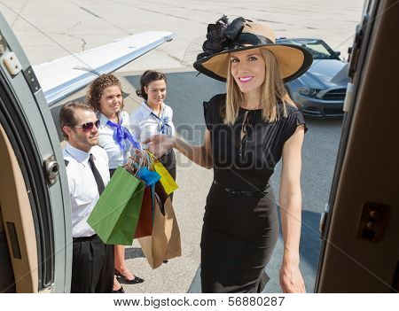 Portrait of smiling rich woman with shopping bags boarding private jet while pilot and airhostess looking at her