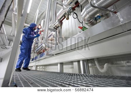 engineer  in mask,gloves,goggles and blue uniform controlling technological system