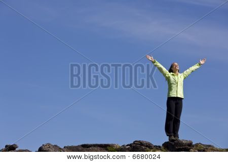 Woman Celebrating Achievement At The Top Of A Mountain