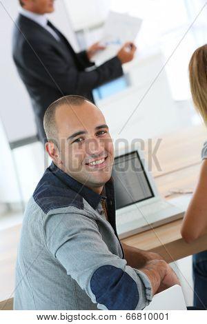 Young man attending management training class