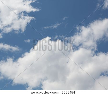 White large fragmentary clouds against the blue sky