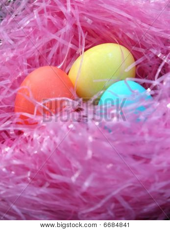 Three Easter eggs in pink grass nest