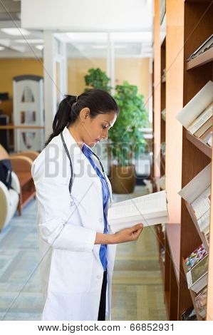 Closeup portrait woman healthcare professional with stethoscope enjoying reading studying in library room poster