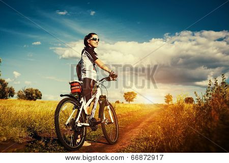 Woman is riding bicycle outside.