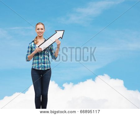 happiness, education and people concept - smiling young woman arrow poiting up over blue sky background