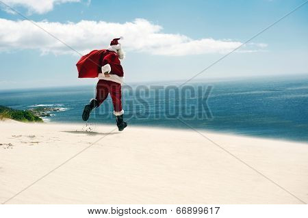 Father Christmas walking along the beach with copyspace