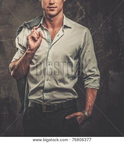 Handsome man in shirt against grunge wall holding jacket over shoulder