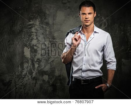 Handsome man in shirt against grunge wall holding jacket over shoulder