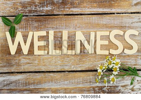 Wellness written with wooden letters, fresh chamomile flowers on rustic surface