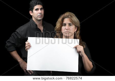 Woman and man holding a white banner with space for text (isolated on black)