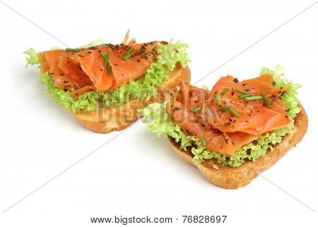 Smoked salmon crostinis on white background. Shallow DoF, focus on RH crostini.