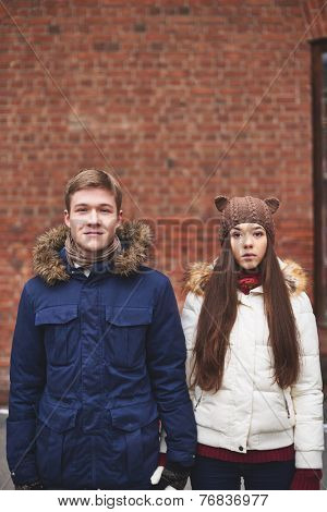 Portrait of young dates in winterwear looking at camera outdoors