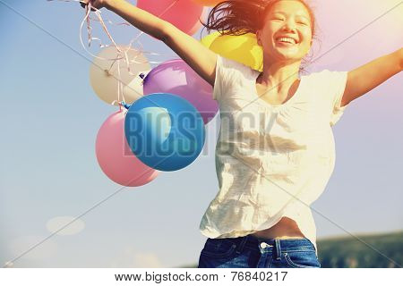 young asian woman jumping on green grassland with colored balloons